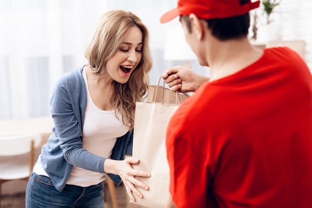 Courier en vêtements orange donne un paquet femme.