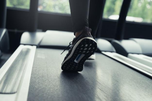 Courir. coureur de mouvement pieds de femme en cours d'exécution sur tapis roulant machine au centre de fitness ou club de santé avec effet de lumière du soleil
