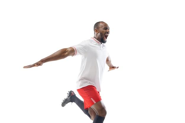 Courir et crier. football professionnel, joueur de football isolé sur le mur du studio blanc.
