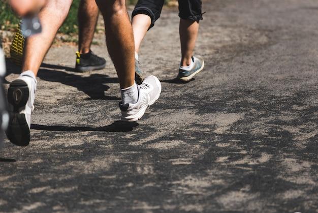 Courir des gens sur des pieds de compétition crossfit sur la route photo en gros