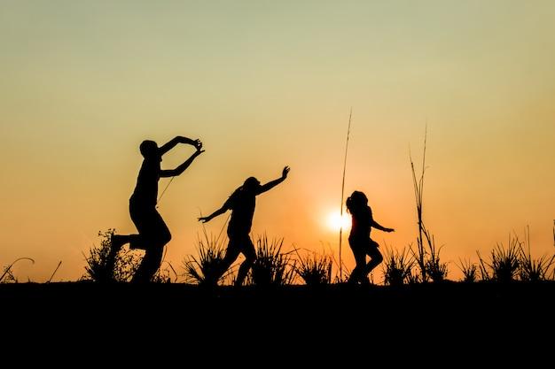 Courir, groupe, enfants, courant, pré, coucher soleil, silhouette