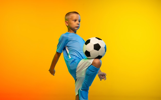 Courir. jeune garçon en tant que joueur de football ou de football en vêtements de sport pratiquant sur studio jaune dégradé