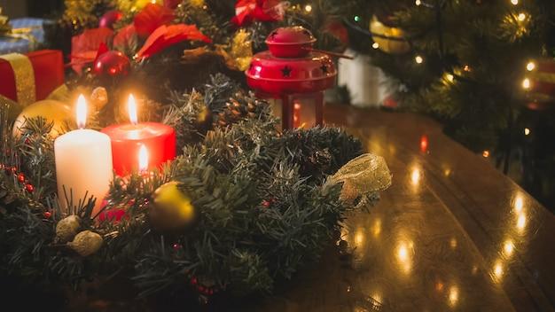 Couronne de l'avent sur table avec des bougies allumées à côté de l'arbre de noël décoré
