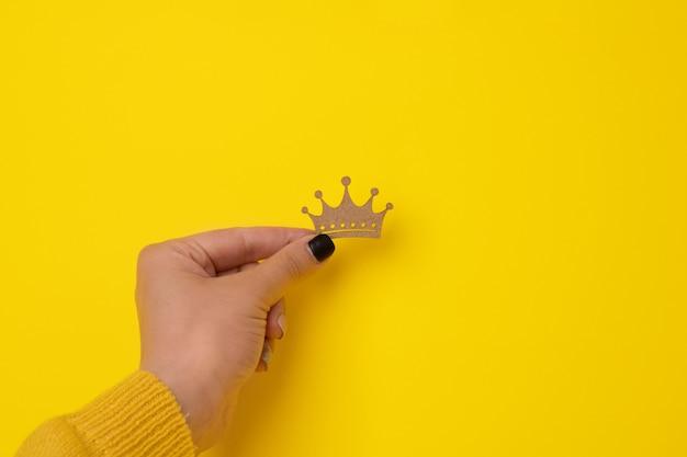 Couronne en bois à la main sur jaune, concept pour roi