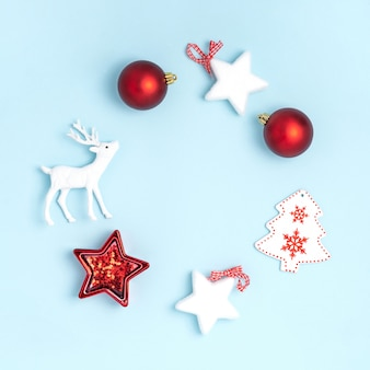 Couronne de boules rouges, étoiles blanches, arbre de noël, cerf sur une surface bleu pastel