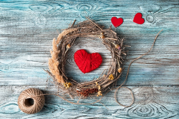 Une couronne de brindilles et d'herbe sèche avec des fleurs et des coeurs rouges sur un fond en bois gris-bleu.