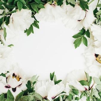 Couronne de cadre de bouquet de fleurs de pivoine blanche sur une surface blanche