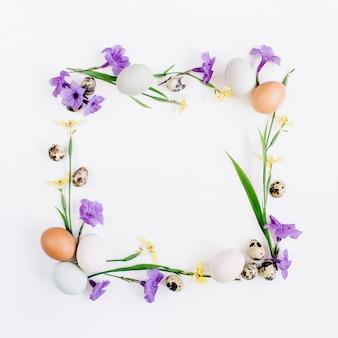Couronne de cadre faite d'oeufs de pâques, oeufs de caille, fleurs jaunes et violettes sur une surface blanche