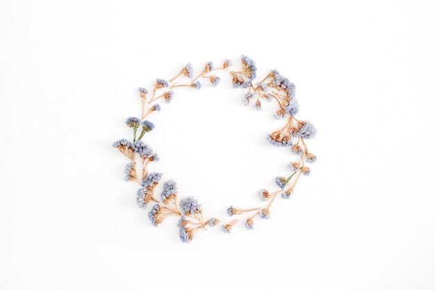 Couronne de cadre de fleurs séchées bleu pâle sur fond blanc. mise à plat, vue de dessus