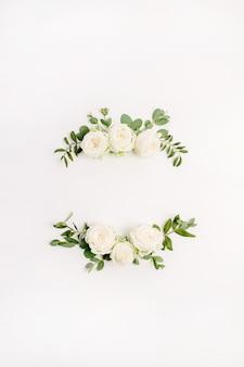 Couronne de cadre floral de boutons de fleurs roses blanches et d'eucalyptus sur blanc