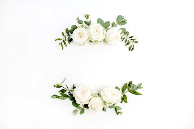 Couronne de cadre floral de boutons de fleurs roses blanches et d'eucalyptus sur fond blanc. mise à plat, vue de dessus