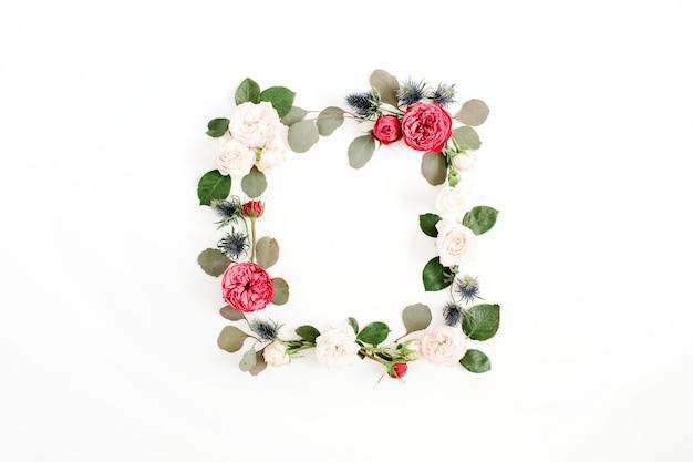 Couronne de cadre rond faite de boutons de fleurs roses rouges et beiges, de branches d'eucalyptus et de feuilles isolées sur fond blanc. mise à plat, vue de dessus