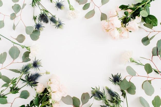 Couronne de cadre rond faite de fleurs roses beiges, fleur d'eringium, branches d'eucalyptus. mise à plat, vue de dessus