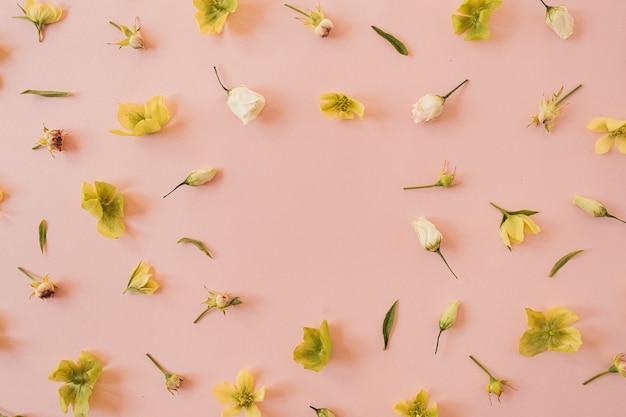 Couronne de cadre rond faite de roses et de fleurs d'hellébore jaune sur rose