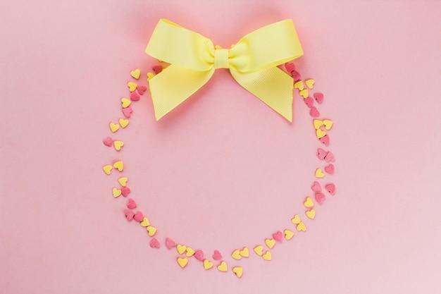 Couronne de confettis jaunes et roses en forme de coeurs et un arc jaune sur un espace de copie de fond rose