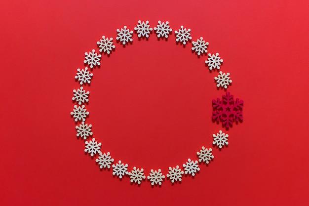 Couronne de décoration de noël circulaire faite de flocons de neige blancs sur une surface rose rouge