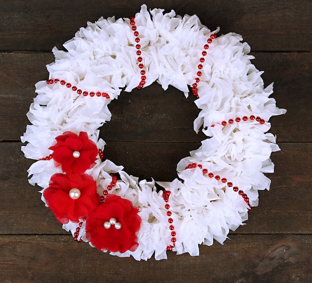Couronne décorative avec des fleurs sur fond de bois