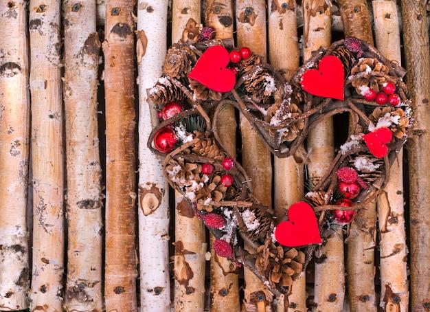 Couronne décorative en forme de coeur de cônes et de brindilles sur des barres en bois