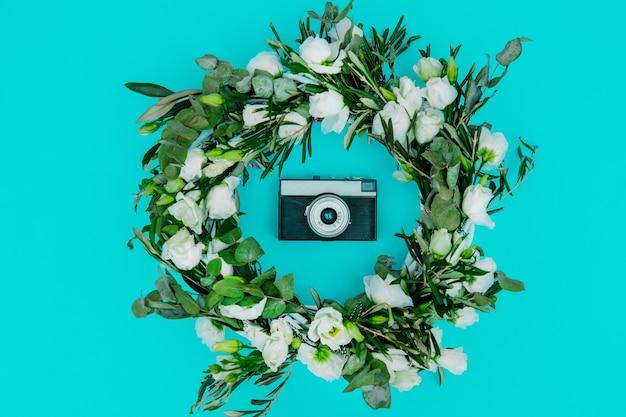 Couronne décorée de roses blanches et appareil photo vintage sur fond bleu. décoré. vue ci-dessus