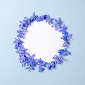 Couronne faite de pétales de fleurs bleues avec espace libre à l'intérieur du cercle sur fond bleu pastel.