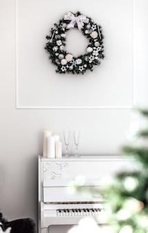 Couronne festive décorative avec des jouets et des boules de noël blancs et argentés dans un intérieur blanc.