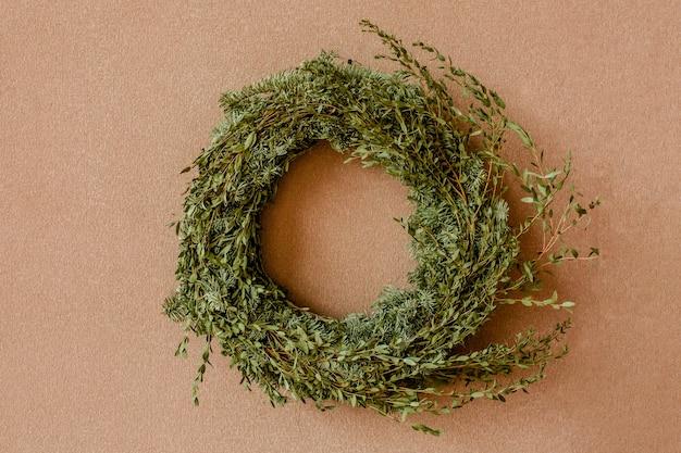 Couronne de fête faite de branches de sapin de noël contre le mur