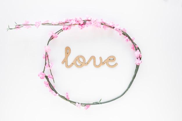 Couronne de fleurs élégante autour de l'inscription de l'amour