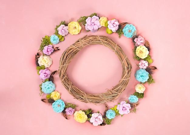 Une couronne de fleurs en papier multicolore sur le fond de corail vivant. saint valentin. concept d'amour. humeur printanière. espace pour le texte. bannière large - image.
