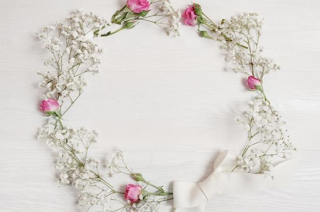 Couronne de fleurs de printemps accroché contre un mur en bois blanc vintage