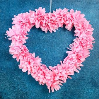 Couronne en forme de coeur décoré de fleurs artificielles fait des serviettes en papier de soie rose