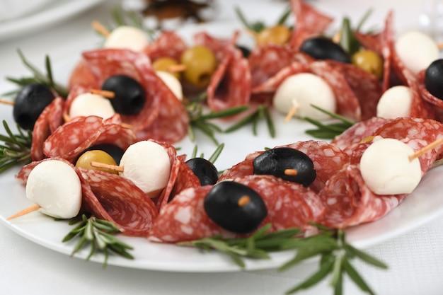 Couronne de noël - antipasti. canapés de salami aux olives, bébé mozzarella.