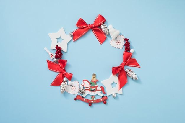 Couronne de noël avec des décorations rouges et blanches sur fond bleu pastel. concept de nouvel an.