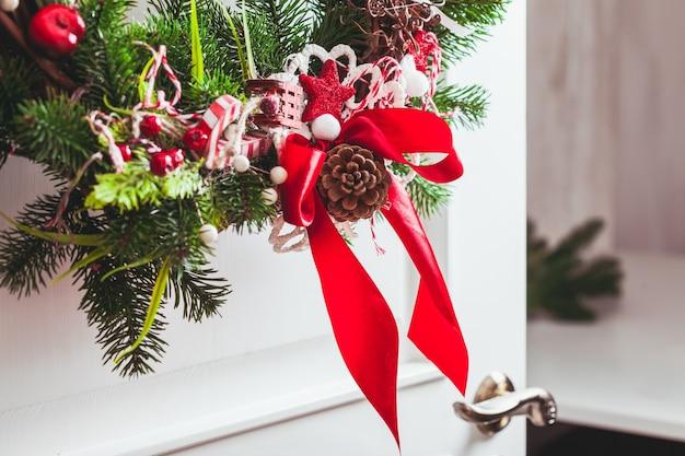 Une couronne de noël est accrochée aux portes blanches. éléments rouges et blancs, arc pour décorer la maison de vacances