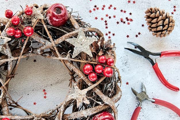 Couronne de noël faite de branches décorées d'étoiles en bois dorées et de bulles de fruits rouges. passe-temps créatif de bricolage. faire des décorations de noël à la main. classe vue de dessus avec pinces métalliques, tenailles