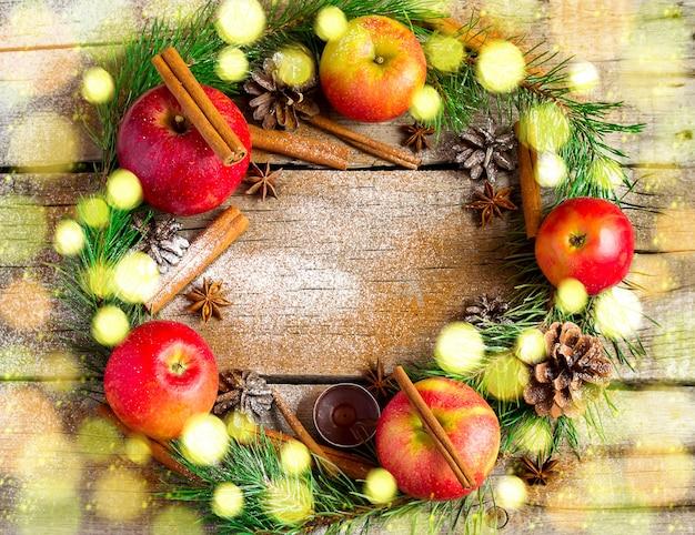 Couronne de noël faite de branches de sapin et de pommes rouges, bokeh. vue de dessus avec espace de copie