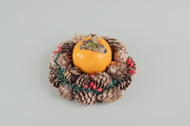Une couronne de noël avec un kaki frais entier.