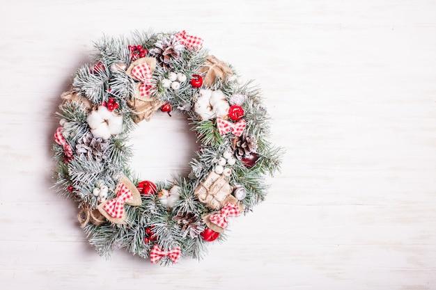 Couronne de noël rouge et blanche avec des arcs et des fleurs de coton