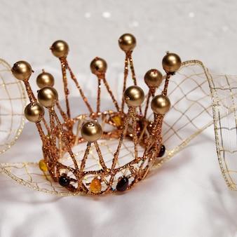 Couronne d'or étincelante pour un carnaval avec un ruban sur fond blanc brillant et soyeux