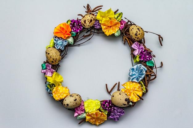 Couronne en osier de pâques fabriquée à la main avec des œufs de caille et des fleurs faites à la main