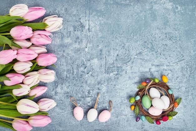 Couronne de pâques, bordure de tulipes roses et oeufs de pâques décoratifs sur fond bleu. vue de dessus, espace copie