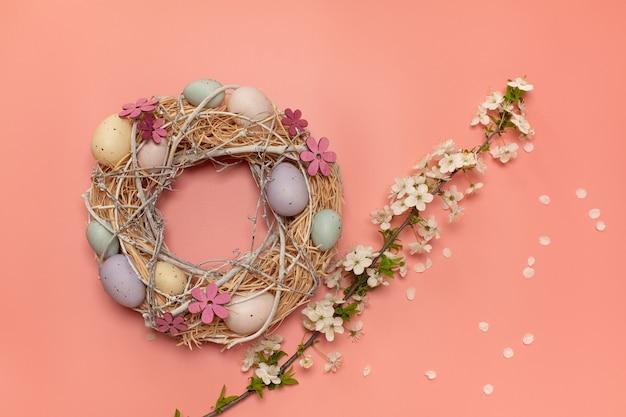 Couronne de pâques faite à la main avec des œufs artificiels colorés et une branche de fleurs printanières fraîches avec des pétales sur fond rose clair