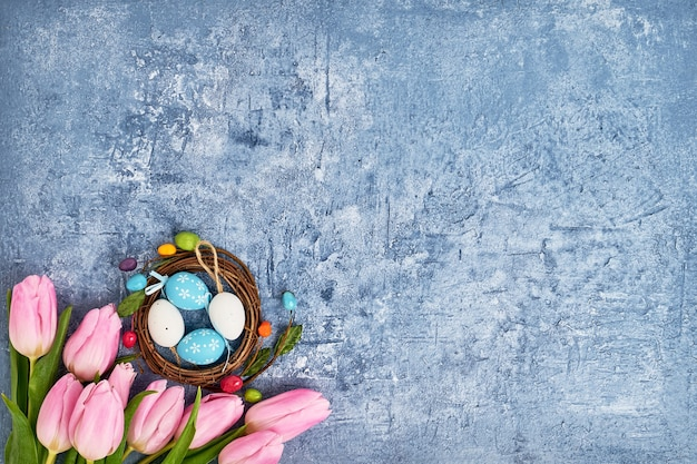 Couronne de pâques, tulipes roses et oeufs de pâques décoratifs sur fond bleu. vue de dessus, espace copie