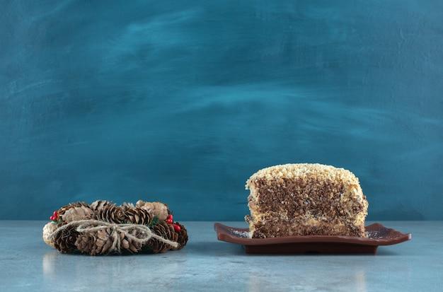 Couronne de pomme de pin à côté d'un plateau avec une tranche de gâteau sur une surface en marbre