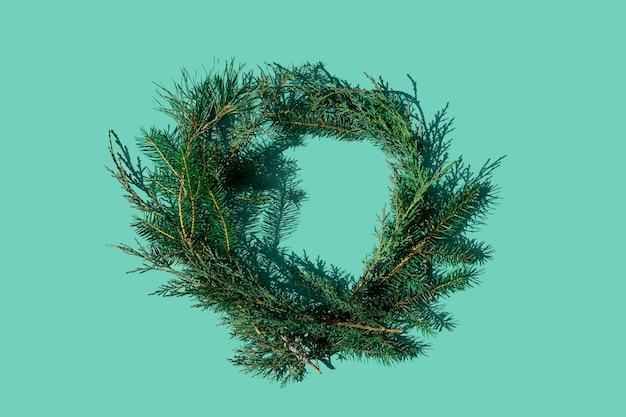 Couronne verte de branches de conifères frais comme le sapin et le pin sur fond menthe avec ombre pour votre projet de noël