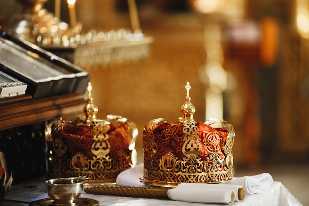 Couronnes rituelles sacrées du mariage dans l'église cathédrale et les bougies rituelles