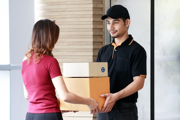 Un courrier asiatique souriant livre des colis à une cliente asiatique à la maison. livraison et expédition de colis, concept d'entreprise de commerce électronique porte à porte.