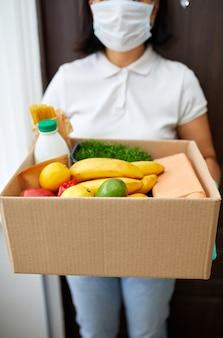 Courrier avec boîte d'emballage avec nourriture, livraison sans contact, coronavirus pandémique de quarantaine de service, femme bénévole en masque de protection blanc et boîte de don de livraison de gants à la maison.