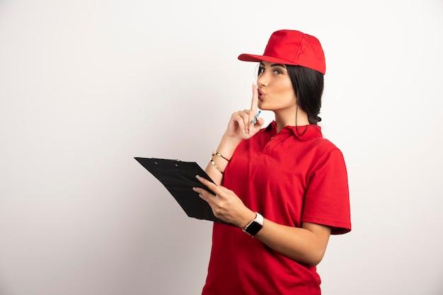 Courrier femelle avec presse-papiers debout faisant signe de silence. photo de haute qualité