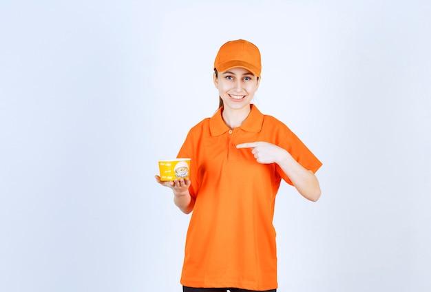 Courrier femelle en uniforme jaune tenant une tasse de nouilles à emporter et pointant vers elle.