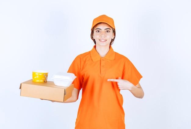 Courrier femelle en uniforme orange tenant des boîtes à emporter jaune et blanc